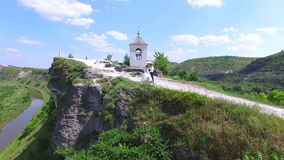 Aerial view of wedding couple having a walk and kissing on a cliff above river stock footage