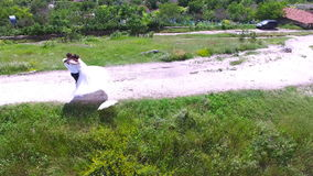 Aerial view of wedding couple having a walk and kissing on a sunny day stock video footage