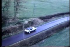 Aerial view of white car driving down rural road stock footage