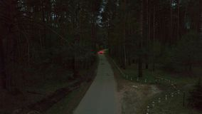 Aerial view white sedan car driving on dark countryside road among summer forest at night. Rear view from drone above car with headlights riding on night road stock video