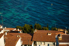 Aerial view of whitewashed houses with red tiles rooftops and sea Stock Image