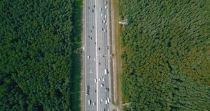 Aerial view on a wide highway with heavy traffic. The camera slowly descends over highway with cars from the height of 450 meters up to 35 meters, accelerated stock video footage