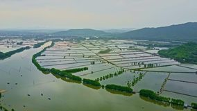 Aerial view wide river under flood against mountains. Aerial view wide river under flood conditions with town houses trees and fields in water against mountains stock video footage