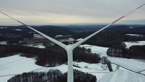 Aerial view of a wind farm in winter. Aerial view of a wind turbine in a snowy winter landscape. Flying through the wings of a