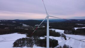 Aerial view of a wind farm in winter. Drone view of a wind turbine in a snowy winter landscape