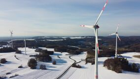 Aerial view of a wind farm in a winter landscape during sunset. Rotating wind turbines during sunset