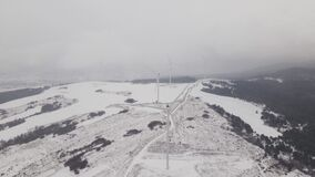 Aerial view of a wind farm in winter, rotating turbines on a snowy field in Ukraine