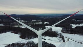 Aerial view of a wind farm in winter. Aerial view of a wind turbine in a snowy winter landscape. Flying above a wind turbine