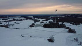 Aerial view of a wind farm in winter. Aerial view of wind turbines standing on a snowy field
