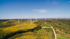 Aerial view of Wind Generating stations in green fields on a background of blue sky. Portugal. Wind Generating stations, in traffic, on a background of blue sky stock photography