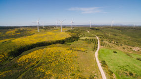 Aerial view of Wind Generating stations in green fields on a background of blue sky. Portugal. Wind Generating stations, in traffic, on a background of blue sky royalty free stock image