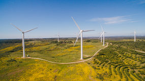 Aerial view of Wind Generating stations in green fields on a background of blue sky. Portugal. Wind Generating stations, in traffic, on a background of blue sky royalty free stock photos
