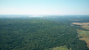 Aerial view of wind generators against smoking stacks of a traditional power plant. Green energy production, new and old Royalty Free Stock Photography