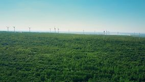 Aerial view of wind generators in forest area. Ecologic energy production stock footage