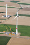 Aerial View : Wind turbines construction site. Aerial View : huge wind turbines construction site close by two cranes in the fields Royalty Free Stock Images