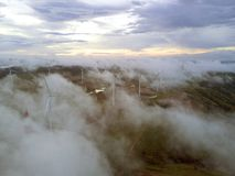 Aerial view Wind turbines and fog for generating electricity in Southeast Asia. Royalty Free Stock Image