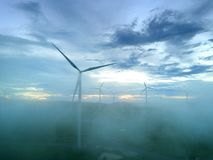 Aerial view Wind turbines and fog for generating electricity in Southeast Asia. Royalty Free Stock Photos