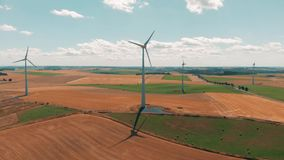 Aerial view of wind turbines and wind gernerators in motion on a summers day over wheat crops with with large open sky stock footage
