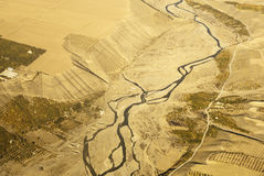 Aerial view of a winding river surrounded by yellow wheat field Stock Photos