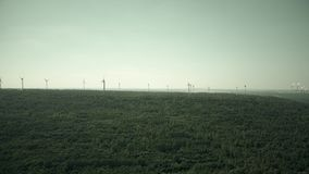Aerial view of windmills and distant smoking stacks of a traditional power plant Royalty Free Stock Photography