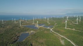 Solar Farm with Windmills. Philippines, Luzon. Aerial view of Windmills for electric power production on the seashore. Bangui Windmills in Ilocos Norte stock video footage