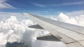 Aerial view through the window of the commercial airplane flying over clouds