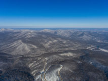 Aerial view of winter mountain forest and road. Royalty Free Stock Photography