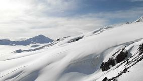 Aerial view of a winter mountain landscape. The snow-covered rocky slopes of the resort of the southern Elbrus region