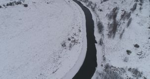 Winter river landscape. Aerial view winter river with snow-covered shore. Flight over the river in winter in the countryside. Aerial footage stock video