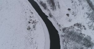 Winter river landscape. Aerial view winter river with snow-covered shore. Flight over the river in winter in the countryside. Aerial footage stock footage