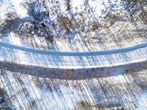 Aerial view of a winter road in the forest. Winter landscape countryside. Aerial photography of snowy forest with road. Captured f. Rom above with a drone royalty free stock photography