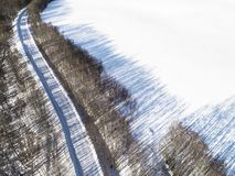 Aerial view of a winter road in the forest. Winter landscape countryside. Aerial photography of snowy forest with road. Captured f. Rom above with a drone stock photos