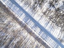 Aerial view of a winter road in the forest. Winter landscape countryside. Aerial photography of snowy forest with road. Captured f. Rom above with a drone stock images