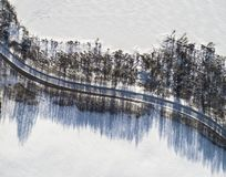 Aerial view of a winter road between two frozen lake. Winter landscape countryside. Aerial photography of snowy forest and frozen. Lake with road. Captured from stock photo