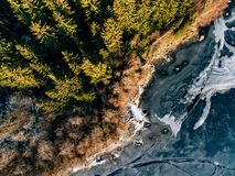 Aerial view of the winter snow forest and frozen lake from above captured with a drone in Finland. Aerial view of the winter snow covered forest and frozen lake Stock Photo