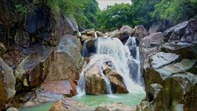 Aerial view woderful waterfall among rocks against jungle. Aerial view wonderful waterfall among large rocks against deep tropical jungle and blue sky in Vietnam stock footage