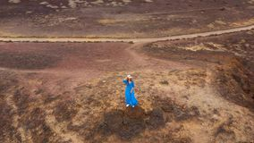 Aerial view of woman in a beautiful blue dress and hat stands on top of a mountain in a conservation area on the shores. Of the Atlantic Ocean. Beautiful nature stock video footage