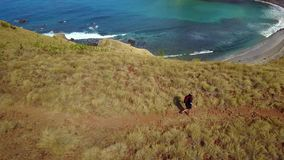 Aerial view of woman hikes hill on Padar Island. Beautiful aerial view footage of a young woman hikes hill on the Padar Island, an island located near Bali stock video