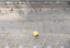 Aerial view of woman holding yellow umbrella walking through car parking. With red traffic cone Stock Image