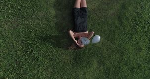 Aerial view of woman lying on the grass while drone is taking off the sunglasses from her face. Aerial top view of happy woman relaxing on the grass during sunny stock footage