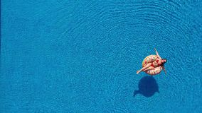 Aerial view of a woman in red bikini lying on a donut in the pool. Concept of summer rest and relaxation stock video