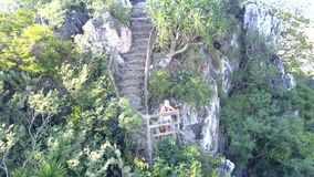 Aerial view woman rests on ground at old stone steps. Aerial view young woman rests on little ground at old stone steps among wild jungle on mountain stock video