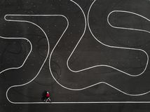 Aerial view of a woman riding a bike on a parking lot. Zigzag track lines on the asphalt stock image
