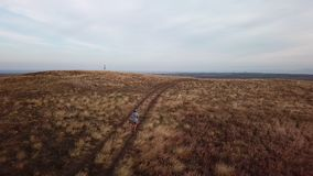 Woman running on country road through dry land and hills. Aerial view of a woman running on country road through dry land and hills stock video