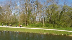 Aerial view of woman running by the lake, with people sitting on benches. stock footage