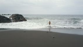 Aerial view of a woman running into water on a black sand beach of Tenerife, Spain. Ocean waves break and create white. Aerial Top View of Canary Islands stock footage
