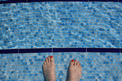 Aerial view of a woman's feet going into luxury swimming pool. Aerial view of a woman's feet with going into luxury swimming pool with crystal clear water and Stock Image