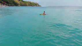 Aerial view of woman on stand up paddle board in blue ocean. Aerial view of woman on stand up paddle board in ocean stock video footage