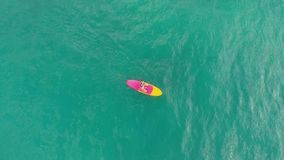 Aerial view of woman on stand up paddle board in blue ocean. Aerial view of woman on stand up paddle board in ocean stock footage