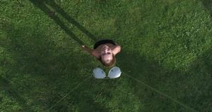 Aerial view of woman standing on the grass while drone is taking off the sunglasses from her face. Aerial top view of happy woman waving to the camera while stock footage